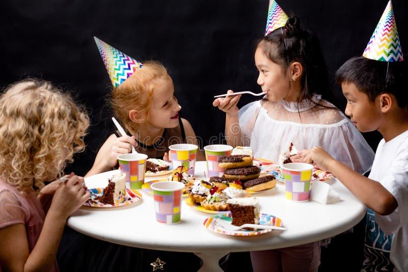 Barn som tillsammans äter och tycker om det inomhus födelsedagpartiet royaltyfri fotografi