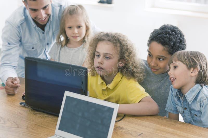 Barn som tillsammans arbetar på bärbara datorn royaltyfri bild