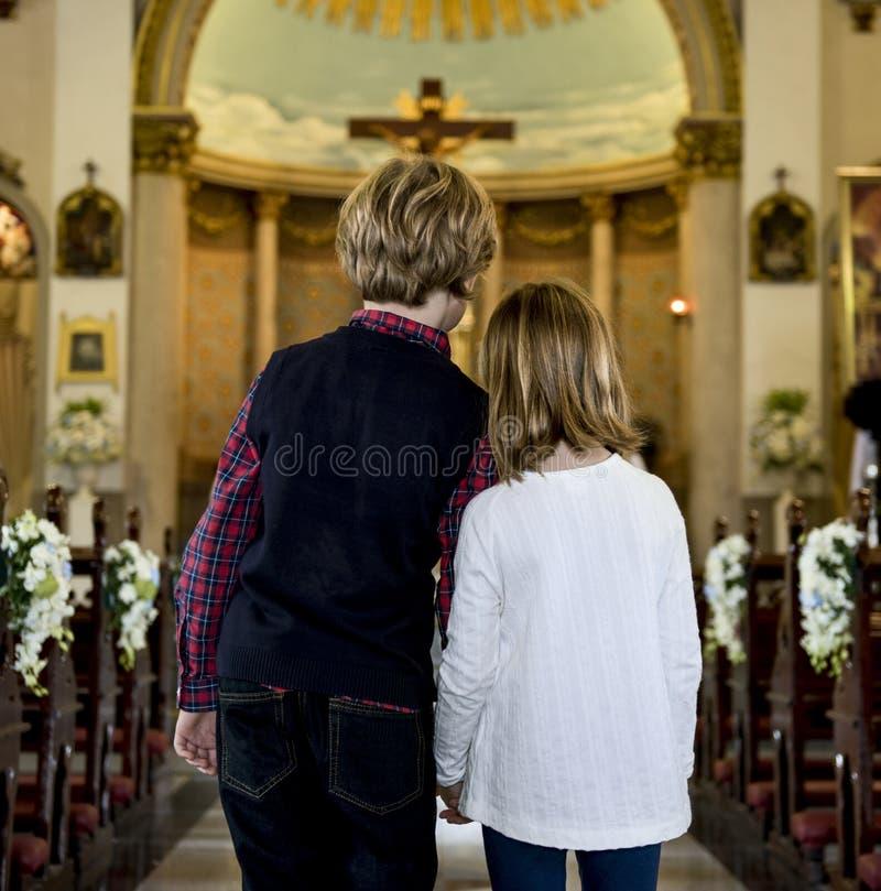 Barn som tillsammans ber insidan en kyrka royaltyfri fotografi