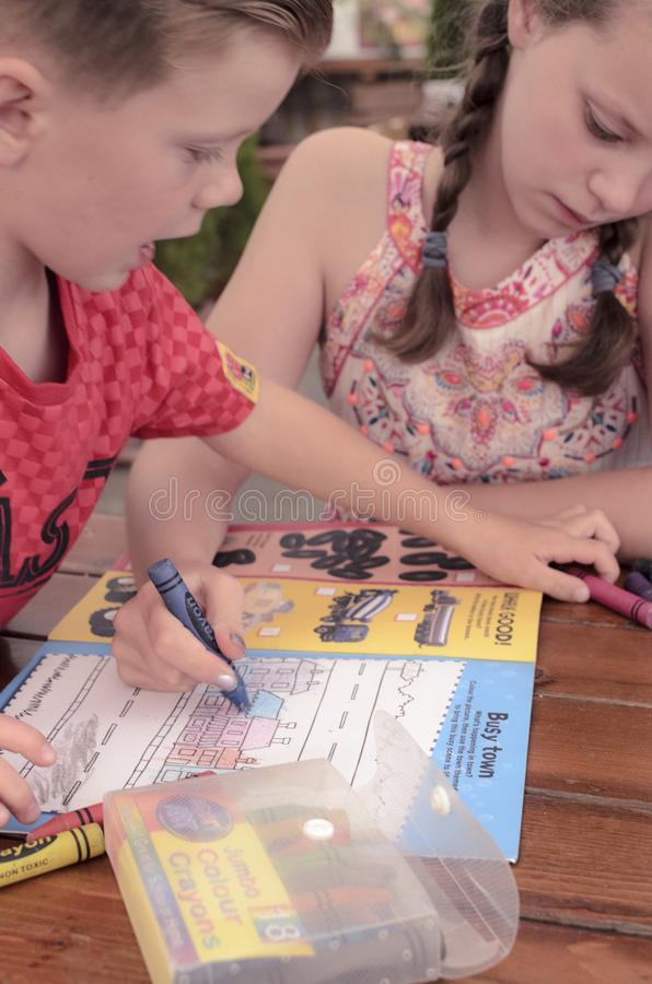 Barn som tillsammans färgar böcker playfully royaltyfria bilder