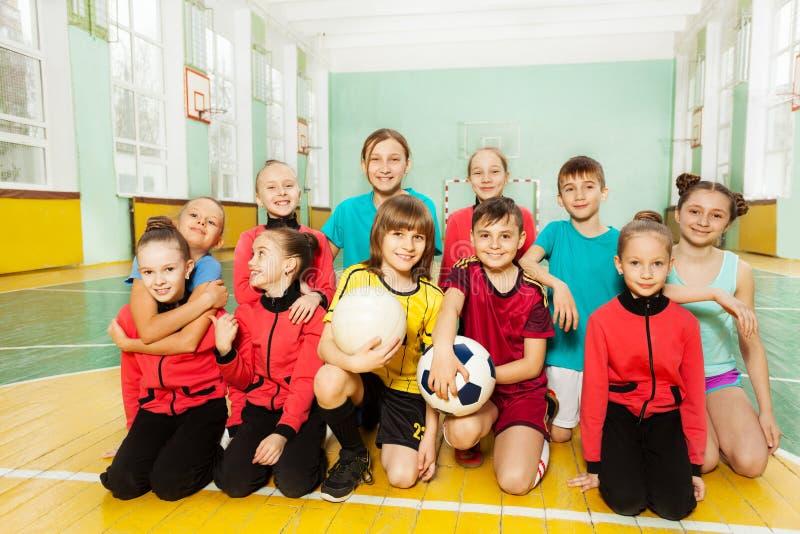 Barn som tillsammans sitter efter fotbollsmatch royaltyfri fotografi