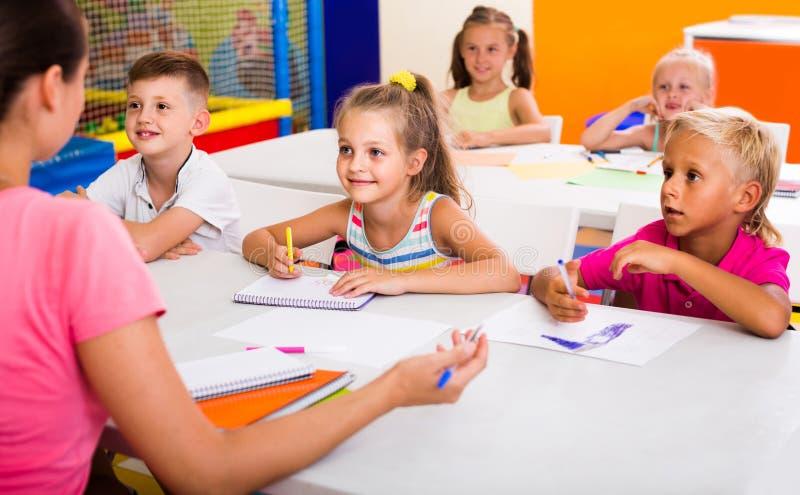 Barn som tillsammans sitter och studerar i grupp på skolan arkivbild