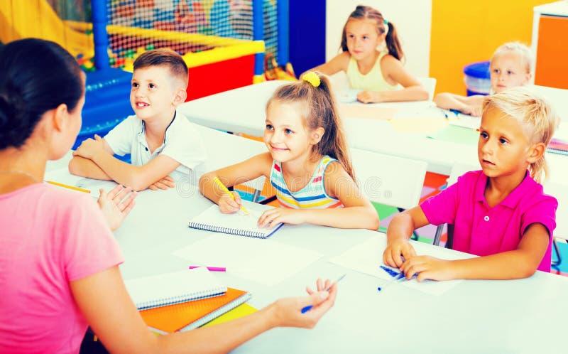 Barn som tillsammans sitter och studerar i grupp på skolan arkivbilder