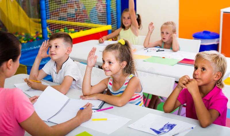 Barn som tillsammans sitter och studerar i grupp på skolan arkivfoton