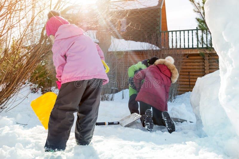 Barn som tillsammans spelar i gård efter snöfall i vinter Grupp av ungar som bilding diagram, och snögubben med skyfflar och andr fotografering för bildbyråer