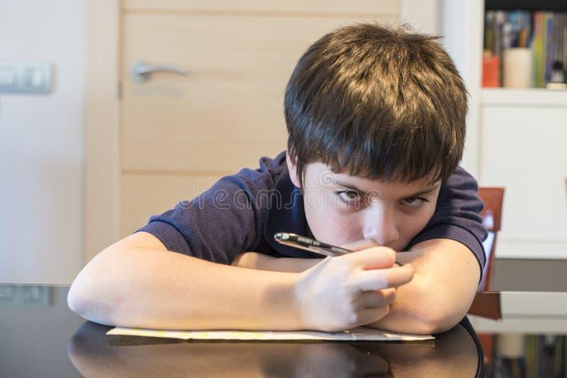 Barn som tröttas av att studera arkivfoto