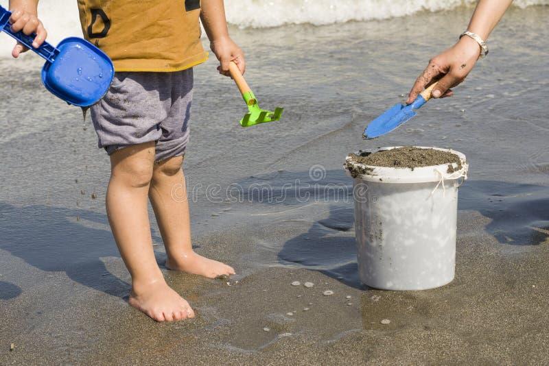 Barn som två tillsammans arbetar för påfyllning av hinken på havskusten royaltyfri bild