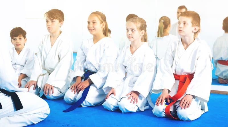 Barn som tycker om deras utbildning med lagledaren på karate arkivbilder