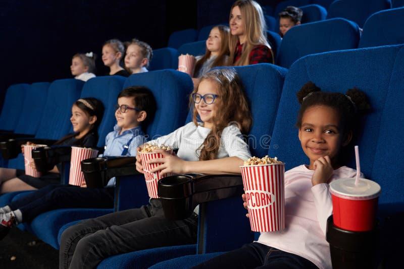 Barn som tycker om filmpremiär i filmteater royaltyfri fotografi