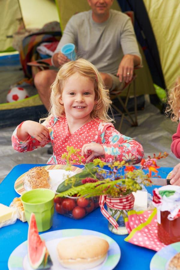 Barn som tycker om picknickstund på campa ferie för familj royaltyfria bilder