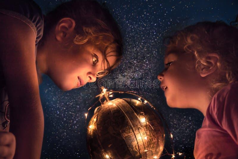 Barn som undersöker natthimmel med astronomi och upptäckten för begrepp för utrymmestjärna- och jordplanet royaltyfri fotografi