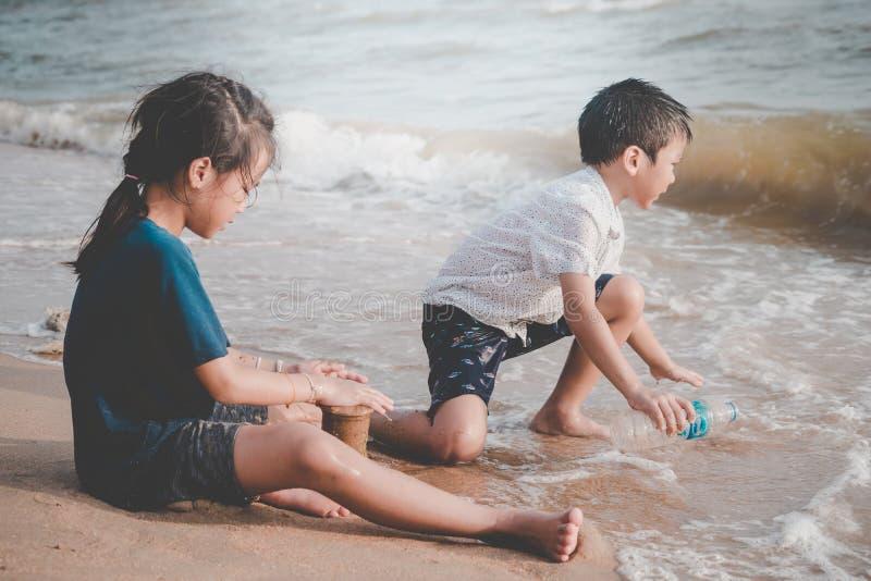 Barn som upp upp gör ren avskräde på stranden för miljö- rent begrepp royaltyfri foto