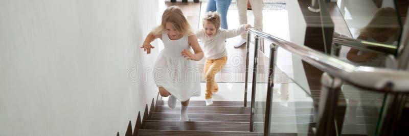 Barn som uppför trappan går till det andra golvet deras nya moderna hus arkivfoton