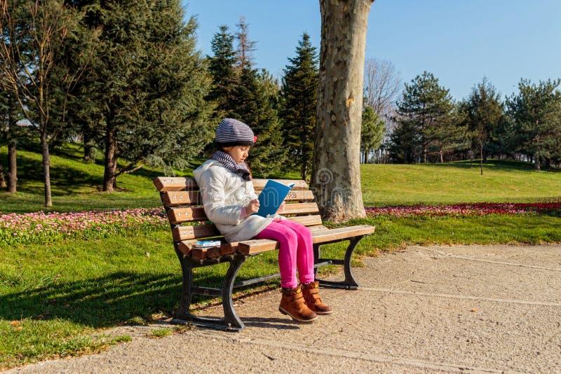 Barn som utomhus läser boken i parkera royaltyfria bilder