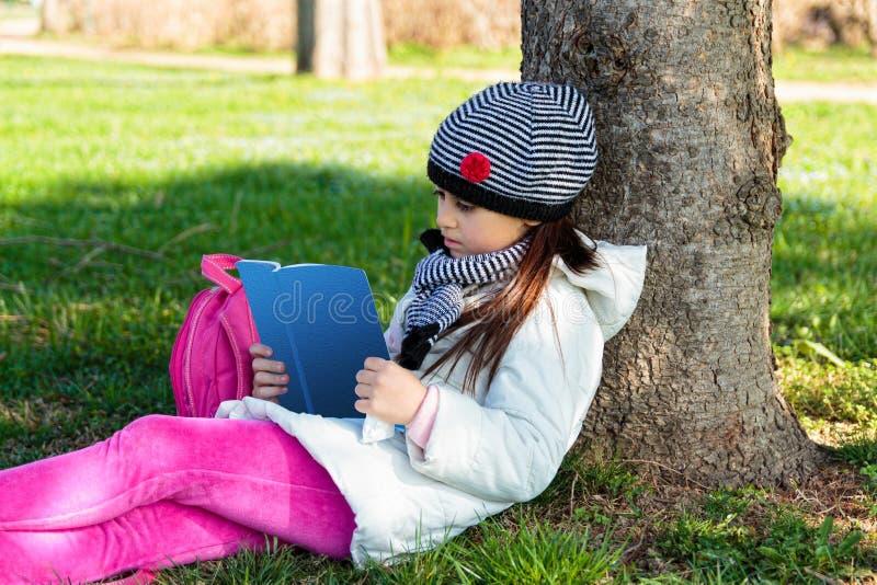 Barn som utomhus läser boken i parkera arkivbild