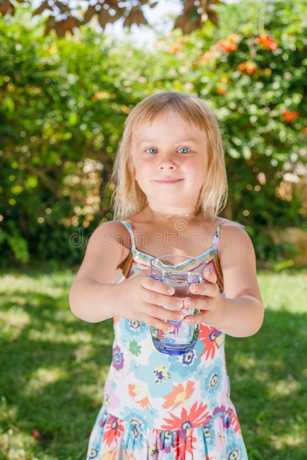 Barn som utomhus rymmer exponeringsglas av dricksvatten royaltyfri foto