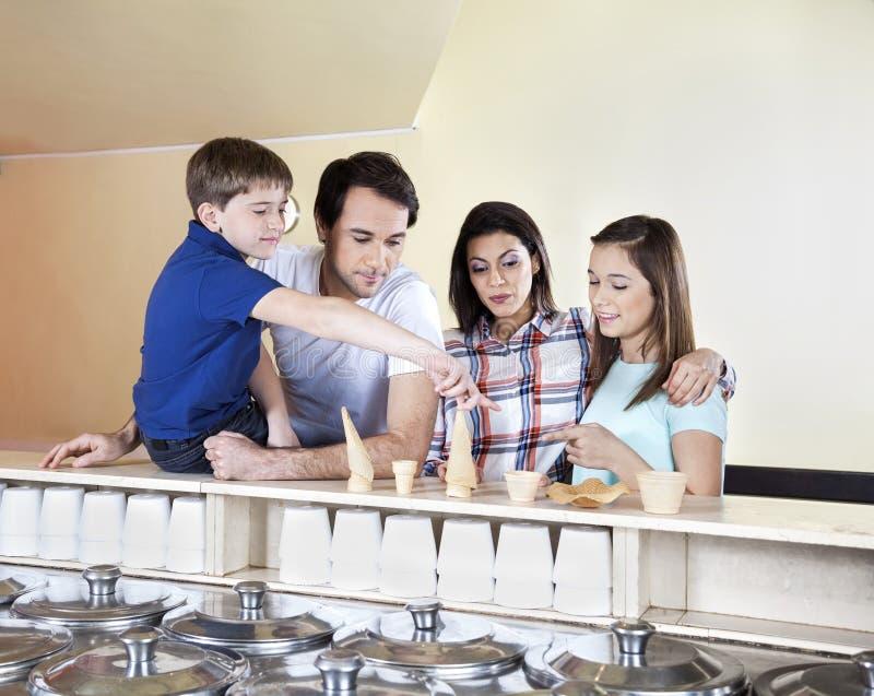 Barn som väljer från glasskoppar och kottar med föräldrar arkivfoto