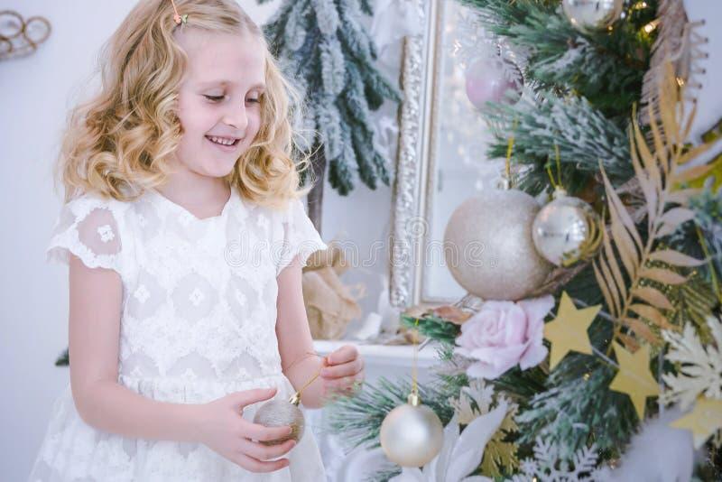 Barn som väntar på det nya året Gullig liten flicka som dekorerar julgranen fotografering för bildbyråer