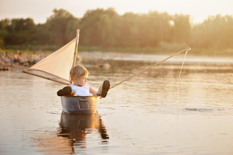 Barn som vilar över vatten i sommarsemester arkivbild