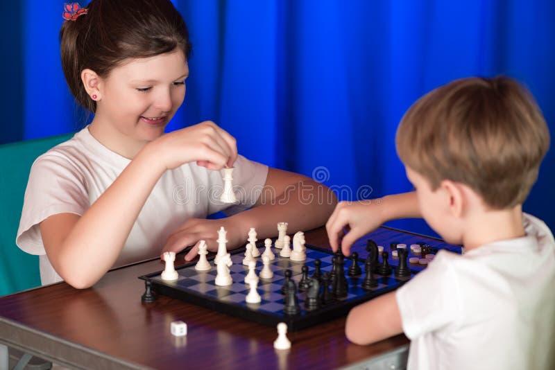 Barn spelar en brädelek som kallas schack arkivfoto