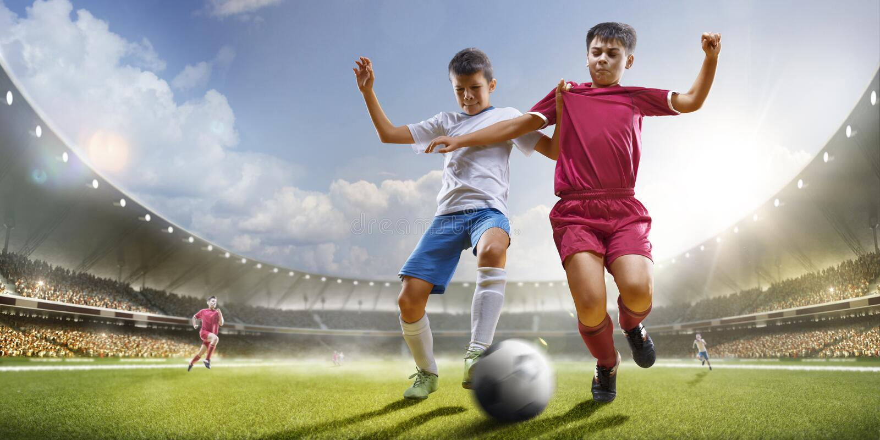 Barn spelar fotboll på den storslagna arenan royaltyfri foto