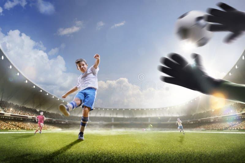 Barn spelar fotboll på den storslagna arenan fotografering för bildbyråer