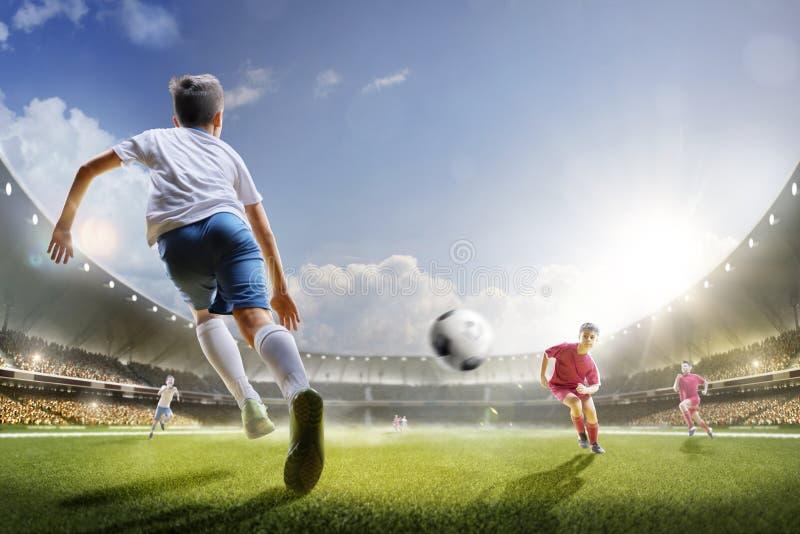 Barn spelar fotboll på den storslagna arenan arkivfoto
