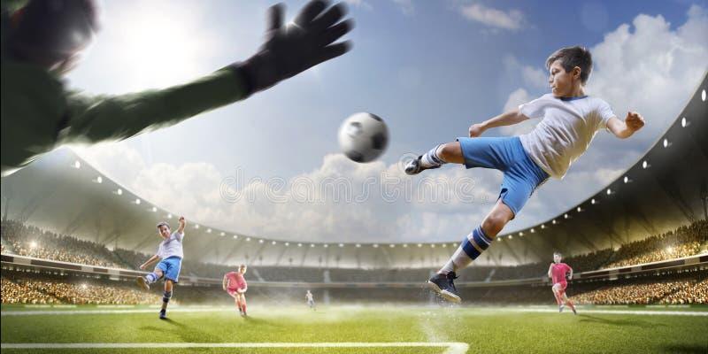 Barn spelar fotboll på den storslagna arenan arkivbilder