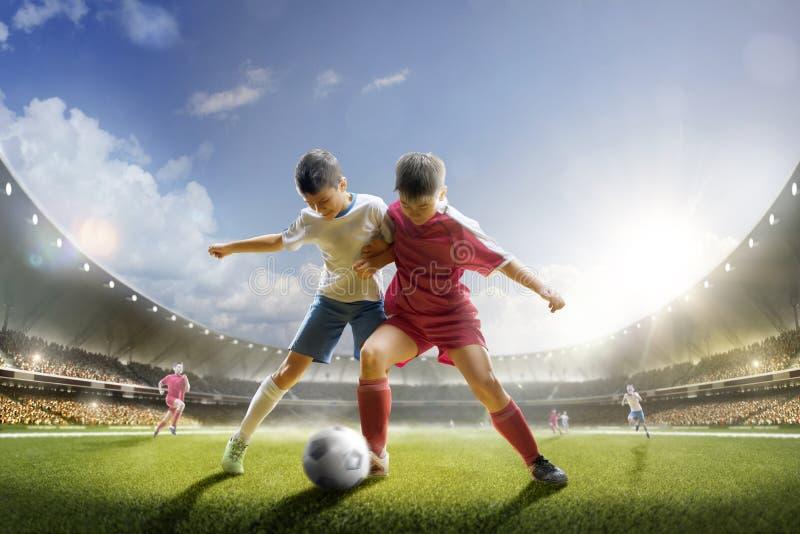 Barn spelar fotboll på den storslagna arenan royaltyfria foton