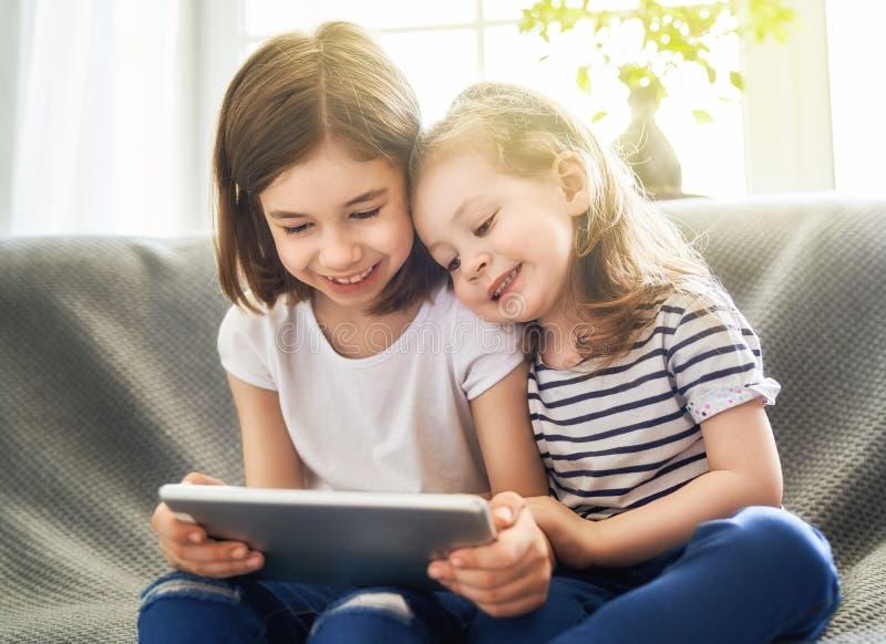 Barn spelar med minnestavlan royaltyfri foto