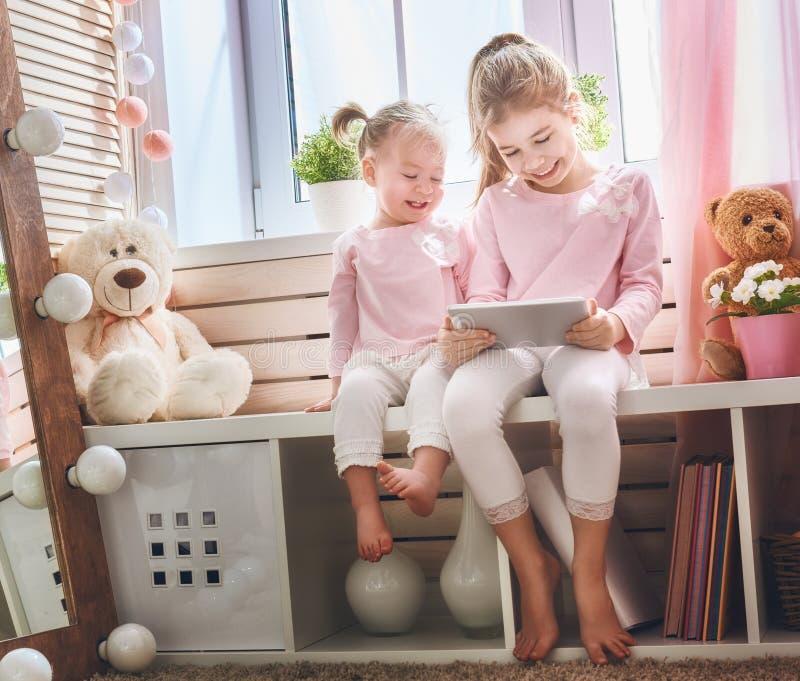Barn spelar med minnestavlan royaltyfria foton