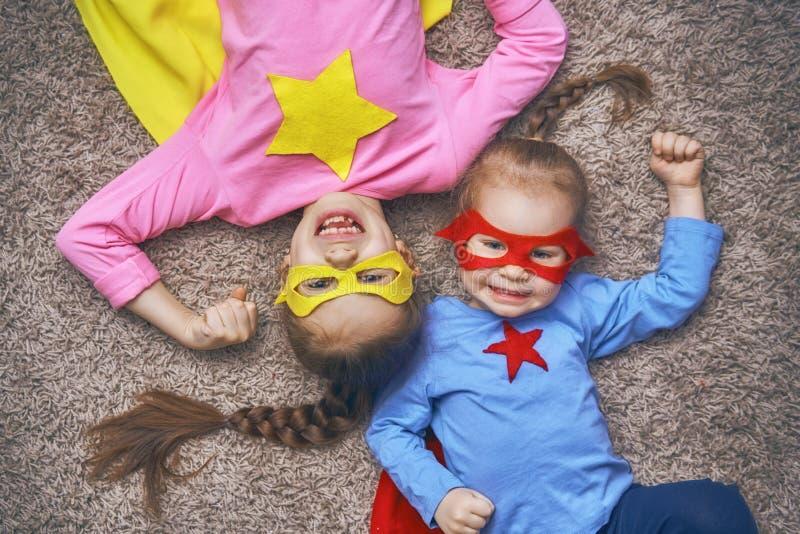 Barn spelar superheroen arkivfoto