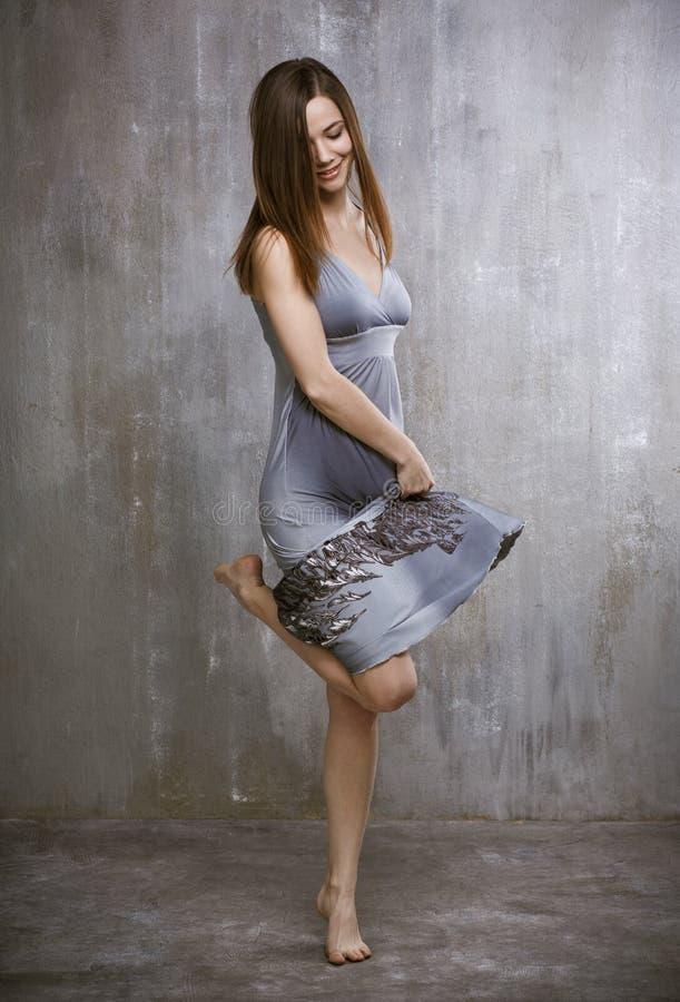 Barn spenslig flicka i en lång klänning som dansar på bakgrundsnollan royaltyfri fotografi
