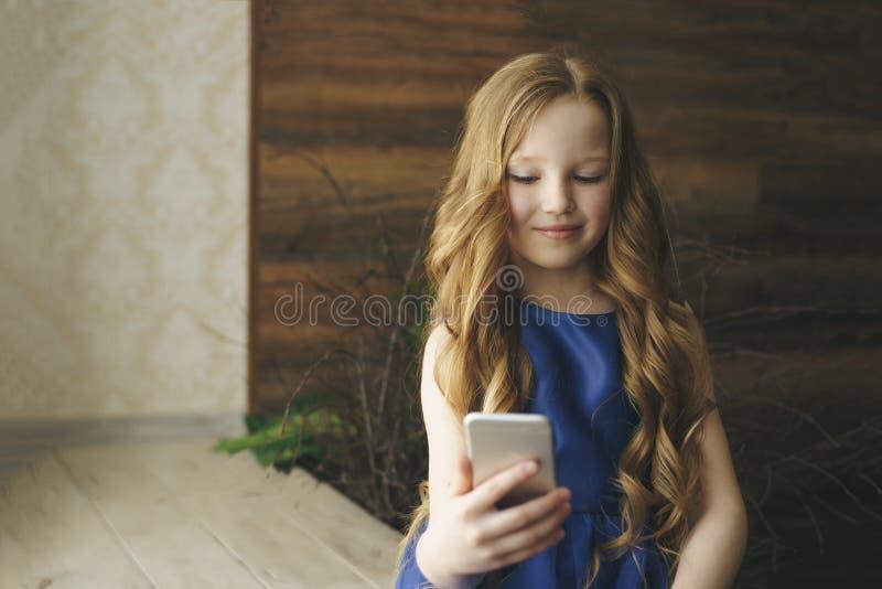 Barn-, teknologi- och kommunikationsbegrepp - le flickan som hemma smsar på smartphonen arkivfoto