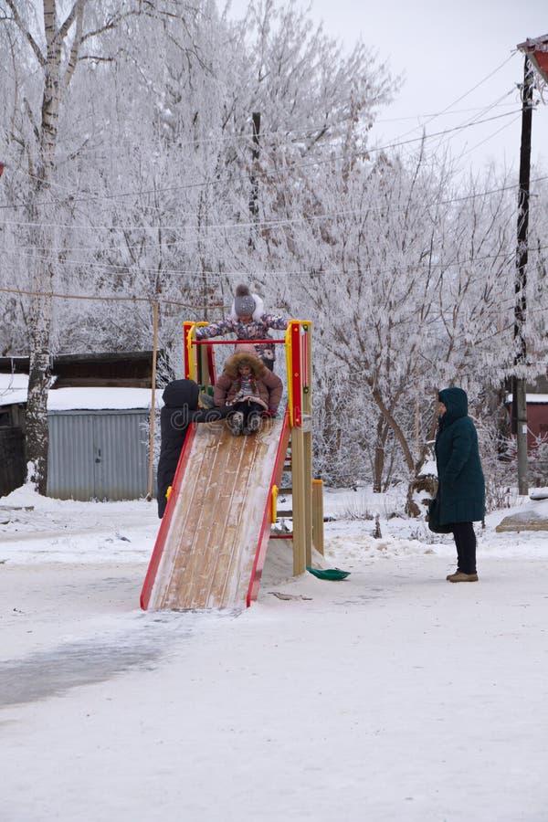 Barn två flickor åker på vintern med en träglidning under kontroll av vuxna. arkivbilder