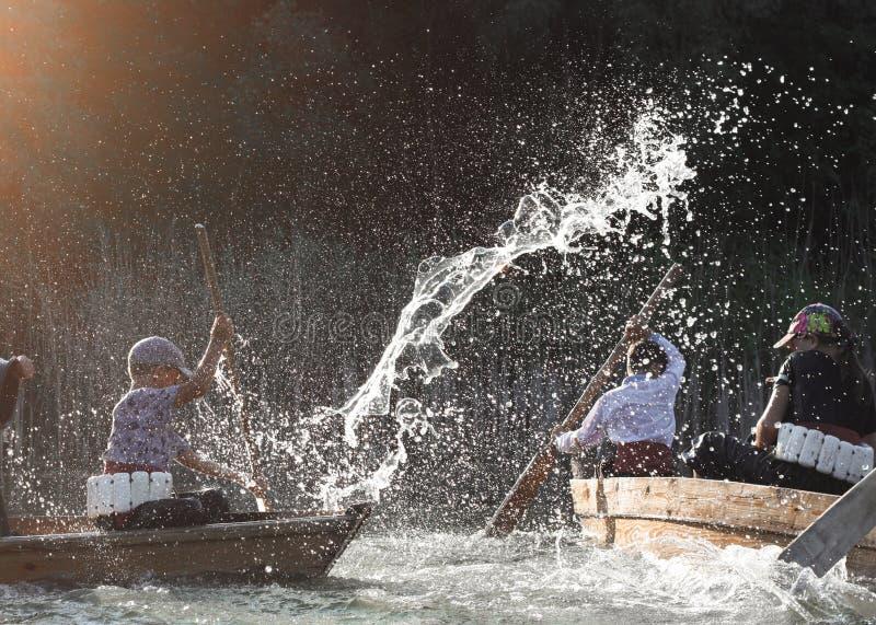 Barn under sprejen av vatten i de sväva fartygen arkivfoton