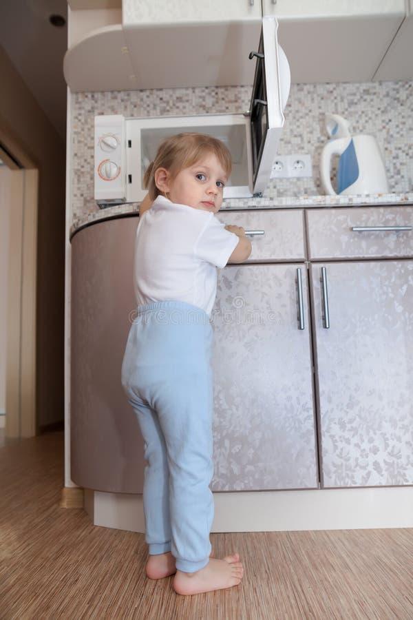 Barn utan övervakning av föräldrar som spelar med mikrovågen arkivbild
