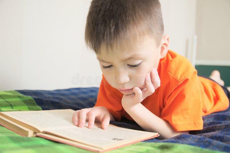 Barn utbildning, pojkeläsebok som ligger på säng, barnstående som ler med boken, utbildning, intressant sagobok royaltyfria foton