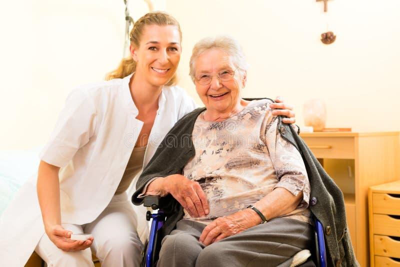 Barn vårdar och den kvinnliga pensionären i vårdhem arkivbilder