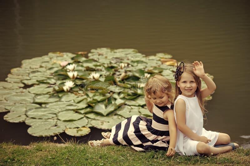 Barn vilar på sjön Flickavåghanden på dammet med näckrons blommar royaltyfri bild