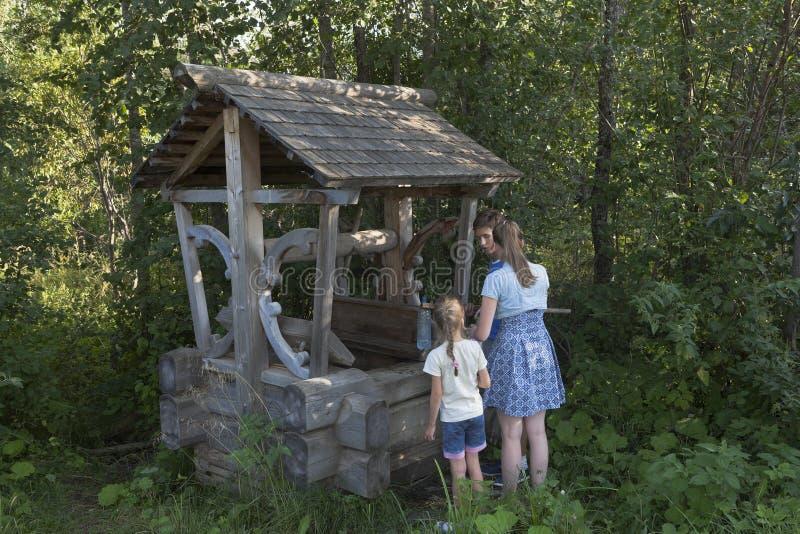 Barn vinner vårvatten från en vår i form av brunnen royaltyfri fotografi