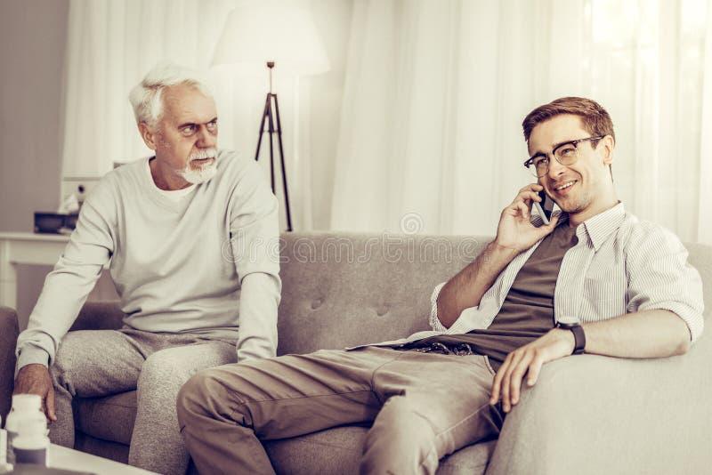 Barn-vuxen människa son som talar över telefonen medan fader som sitter på soffan arkivbild