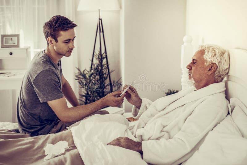 Barn-vuxna människan sonen som räcker termometern till hans som dåligt åldras, avlar royaltyfria foton