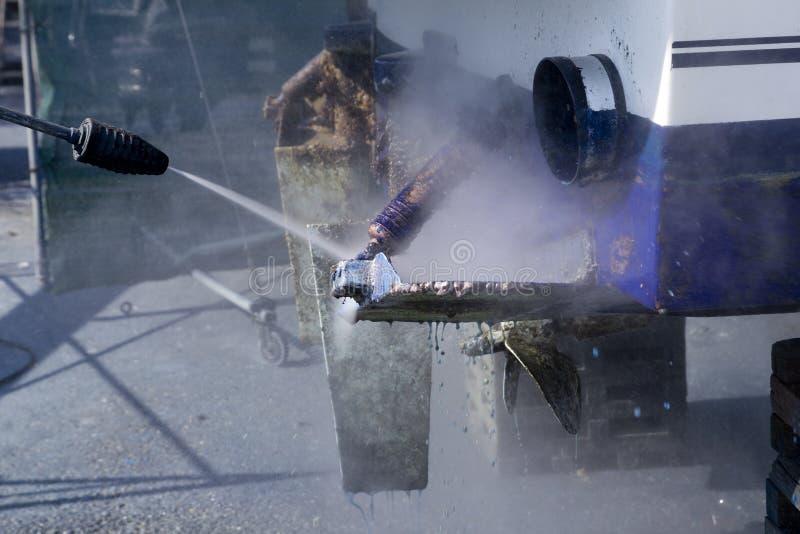 Barnacles azuis da arruela da pressão da limpeza da casca do barco fotografia de stock royalty free