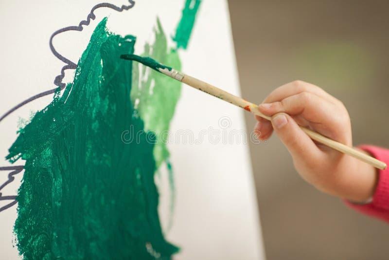 Barnattraktionmålarfärgerna på papper children& x27; s-teckning en hand av t royaltyfria bilder