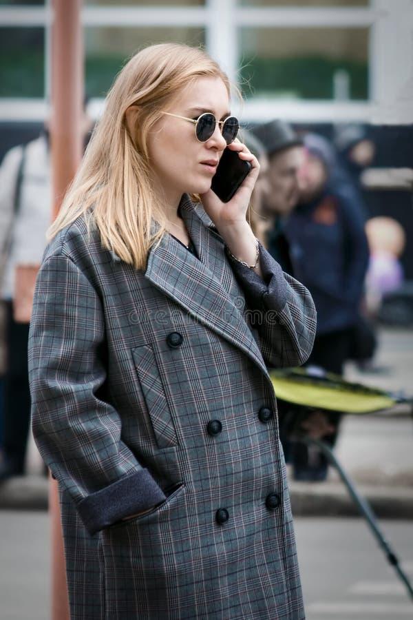 Barnaul,俄罗斯, 2018年5月9日:年轻时髦的妇女谈话在街道上的一个手机 免版税库存图片