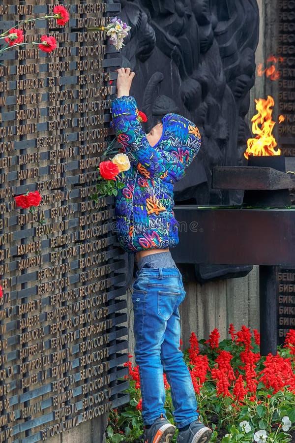 Barnaul, Russia, il 9 maggio 2018: un ragazzino pone i fiori al memoriale di gloria alla fiamma eterna La memoria del caduto immagine stock libera da diritti