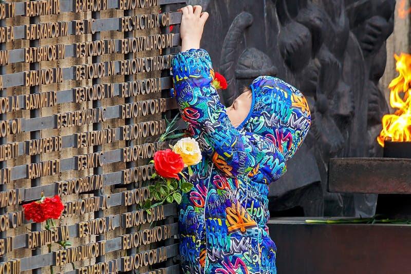 Barnaul, Russia, il 9 maggio 2018: un ragazzino pone i fiori al memoriale di gloria alla fiamma eterna La memoria del caduto fotografia stock libera da diritti