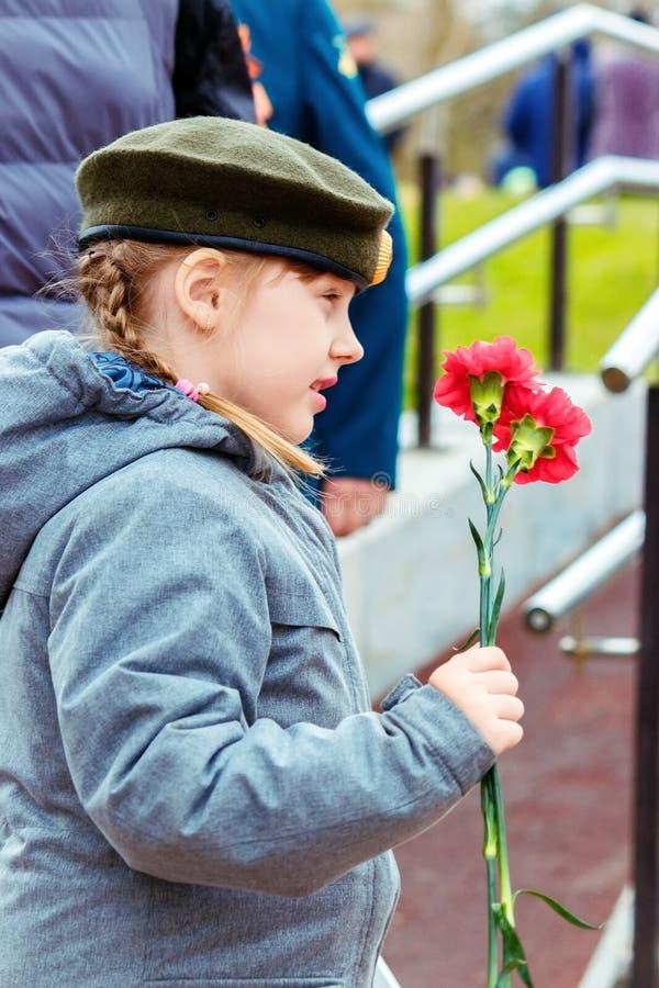 Barnaul, Russia, il 9 maggio 2018: una bambina in un berretto militare con due garofani in sua mano fotografia stock libera da diritti
