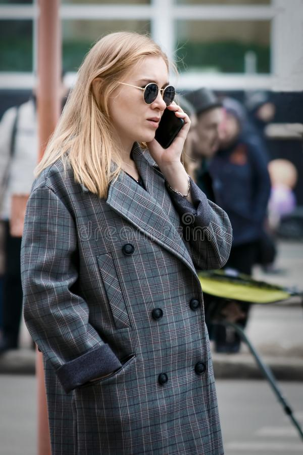 Barnaul, Russia, May 9, 2018: young stylish woman talking on a mobile phone on the street royalty free stock image